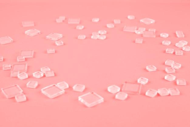 Diversi tipi di cubetti di plastica trasparente sparsi su fondo di corallo Foto Gratuite