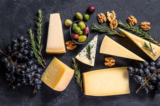Diversi tipi di deliziosi formaggi, noci e uva. vista dall'alto Foto Premium