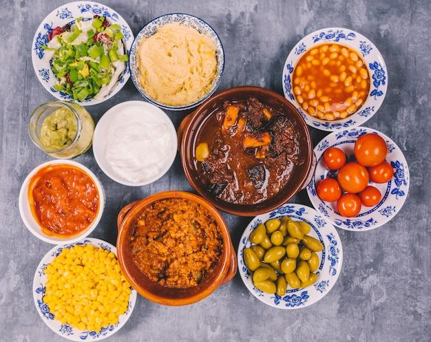 Diversi tipi di deliziosi piatti messicani sul pavimento di cemento Foto Gratuite