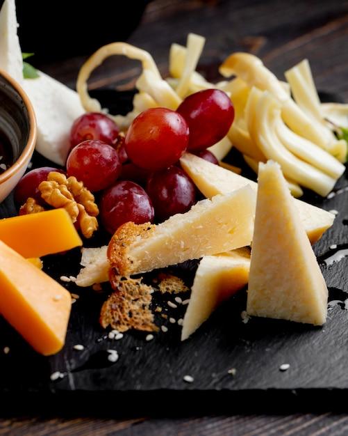 Diversi tipi di formaggio con uva e noci Foto Gratuite