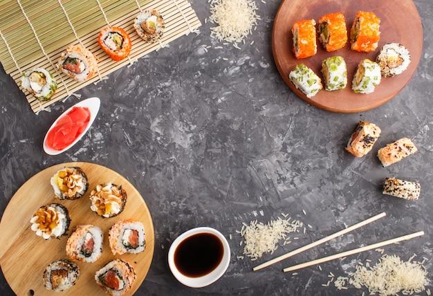 Diversi tipi di involtini di sushi giapponese maki con salmone, sesamo, formaggio, uova e bacchette Foto Premium