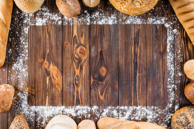Diversi tipi di pane sparsi sul bordo della farina sul tavolo di legno Foto Gratuite