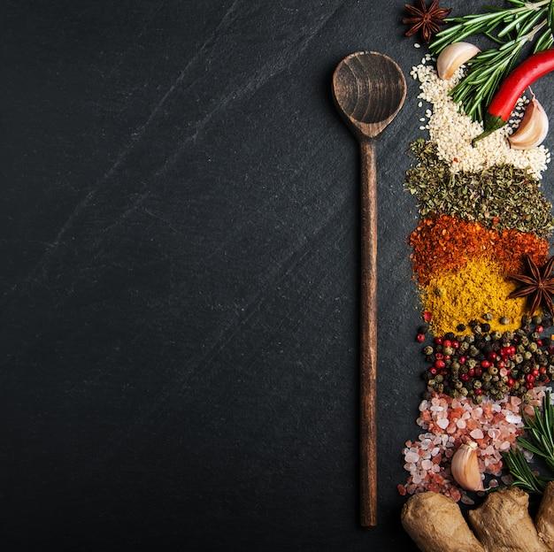 Diversi tipi di spezie su una superficie nera Foto Premium