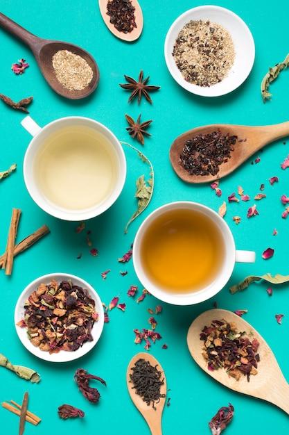 Diversi tipi di tazze da tè bianco con spezie ed erbe sullo sfondo turchese Foto Gratuite