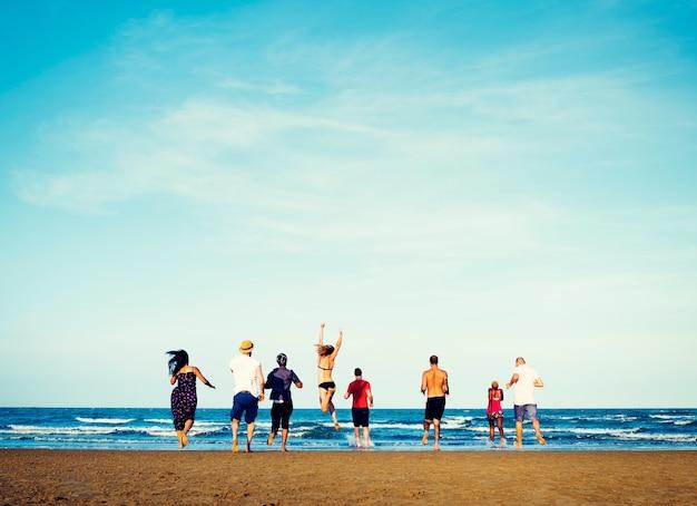 Diverso gruppo di amici che corrono verso la spiaggia Foto Gratuite