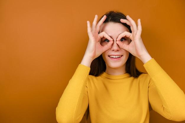 Divertente giovane donna sorridente divertirsi facendo occhiali forma con le mani Foto Premium