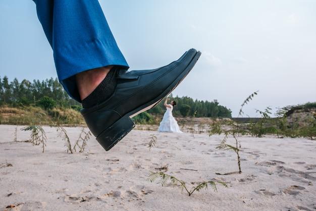 Divertente sposa asiatica e sposo caucasico posting scherzo con i piedi in alto Foto Gratuite