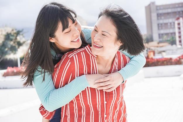 Divertiresi asiatico della figlia e della madre all'aperto Foto Premium