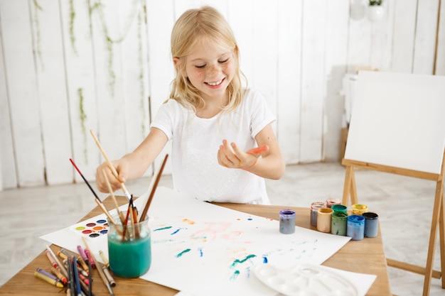 Divertirsi, gioioso, sorridente con i denti ragazza bionda di sette anni che gocciola vernice su un foglio di carta bianca distesa su un tavolo. bambino creativo divertirsi, godersi la pittura. Foto Gratuite