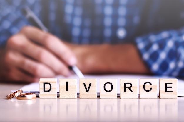 Divorzio. parola da lettere di legno con anelli e un uomo che firma l'accordo sullo sfondo Foto Premium