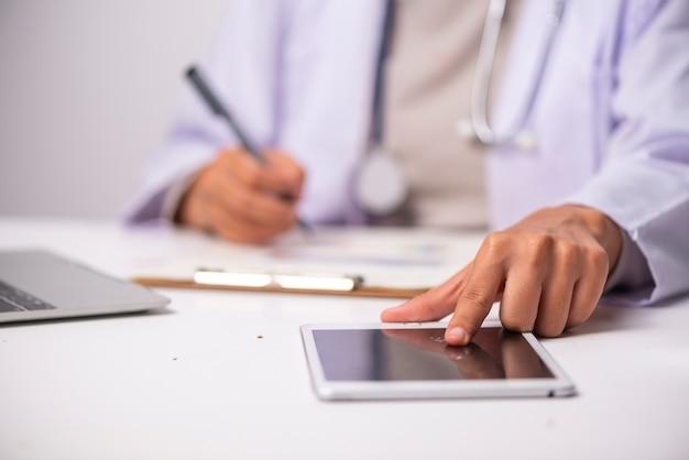 Docter e stetoscopio sulla tabella bianca, concetto di sanità Foto Premium