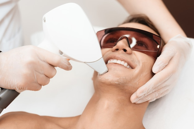 Doctor tratta il viso di un uomo con un moderno epilatore laser Foto Premium