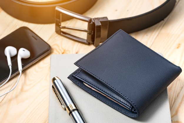 Documenti, penna, cintura e un portafoglio di pelle su una scrivania di legno. Foto Premium