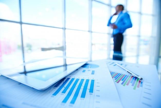 Documenti statistica con uomo d'affari sfondo sfocato Foto Gratuite