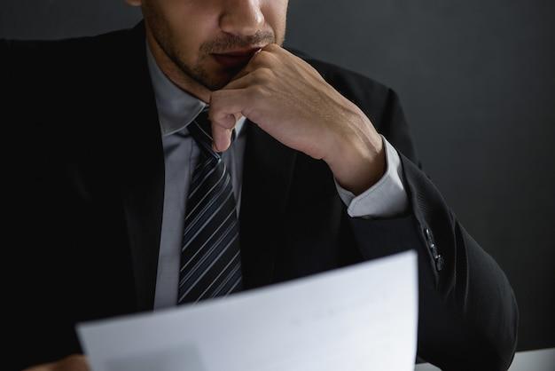 Documento serio della lettura dell'uomo d'affari e meditare Foto Premium