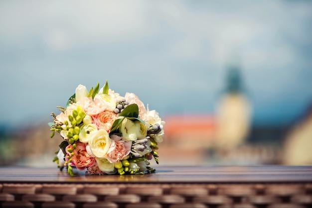 Dolce bouquet da sposa di peonie bianche e rosa si trova su un tavolo Foto Premium