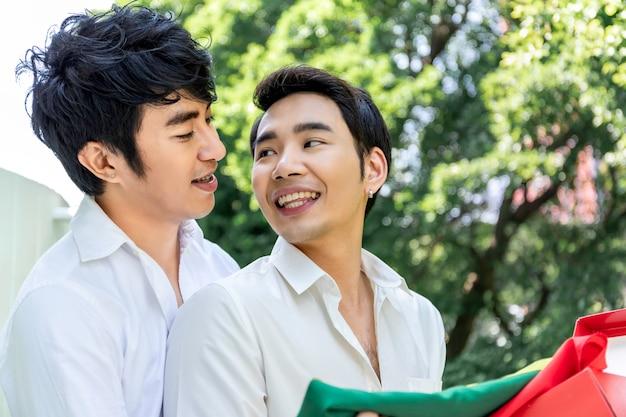 Dolce momento d'amore.ritratto di coppia omosessuale asiatica abbraccio e scatola regalo a sorpresa per il fidanzato.concetto lgbt gay. Foto Premium