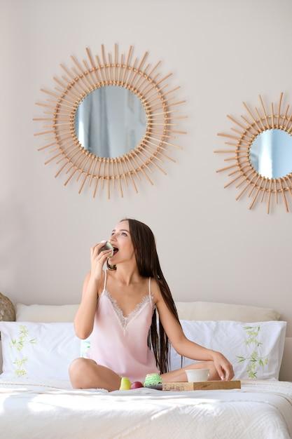 Dolce mordace della bella ragazza mentre facendo colazione a letto Foto Premium