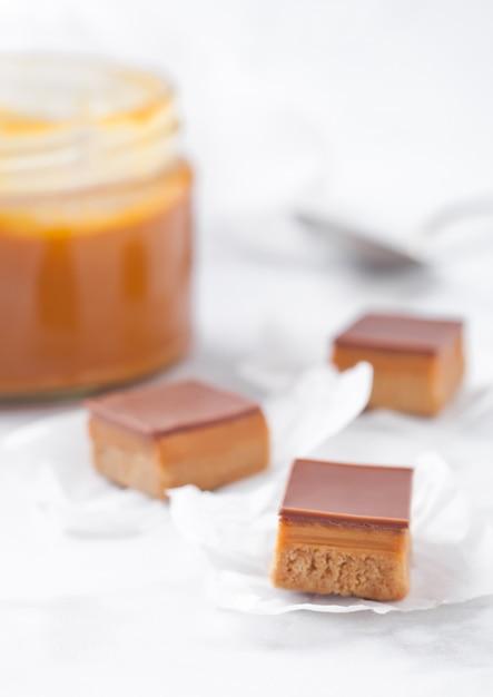 Dolcecuore al caramello e biscotto morde il dessert sul bordo di marmo con un barattolo di caramello salato Foto Premium