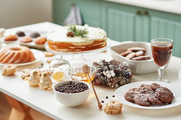 Dolcetti di natale sul tavolo: cupcake, torta nuda, biscotti e caffè con miele Foto Premium