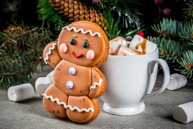Dolcetto natalizio tradizionale. cioccolata calda con marshmallow, biscotto di pan di zenzero, rami di abete e copyspace decorazioni natalizie Foto Premium