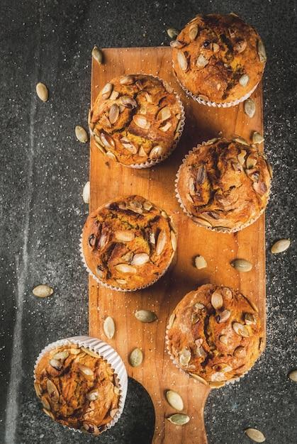 Dolci al forno autunnali e invernali muffin di zucca sani con semi di zucca spezie tradizionali caduta tavolo in pietra nera Foto Premium