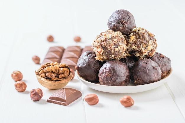 Dolci fatti in casa da noci, frutta secca e cioccolato su un tavolo di legno bianco. Foto Premium