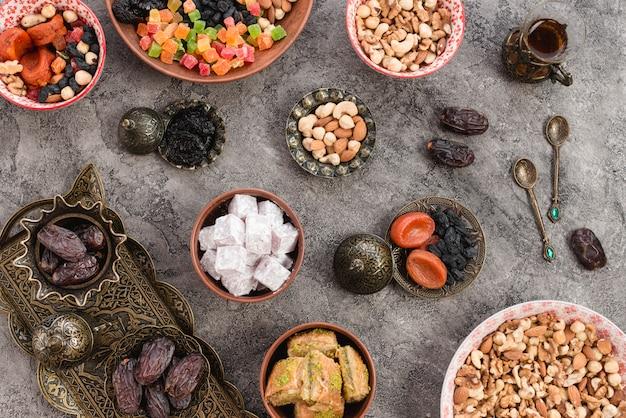 Dolci fatti in casa delizia turca con frutta secca e noci con cucchiai su sfondo concreto Foto Gratuite