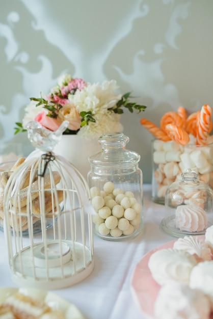 Dolci, noci nello zucchero, caramelle gommosa e molle, meringa - barretta di cioccolato al matrimonio. decor, tavolo dolce Foto Premium