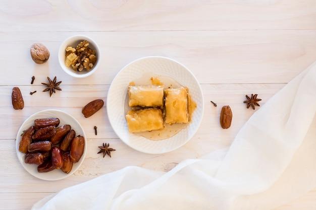 Dolci orientali con frutta data e noci sul tavolo Foto Gratuite