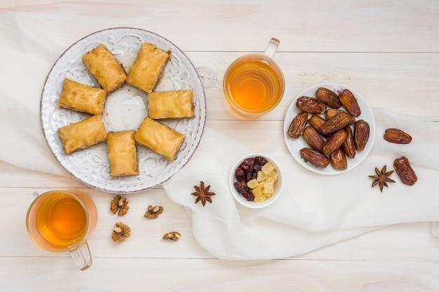 Dolci orientali con frutta data e tazze da tè Foto Gratuite