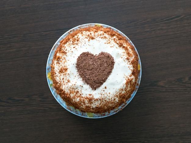 Dolci per san valentino. torta fatta a mano con glassa di crema di formaggio e un cuore di cioccolato. concetto di san valentino. Foto Premium