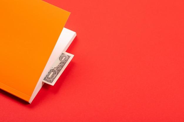 Dollaro come segnalibro nel libro arancione isolato su rosso Foto Premium
