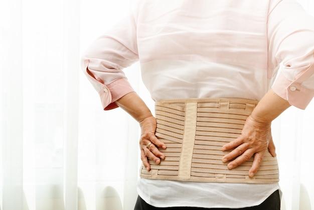 Dolore alla schiena, donna senior che indossa la cinghia di sostegno posteriore su fondo bianco Foto Premium