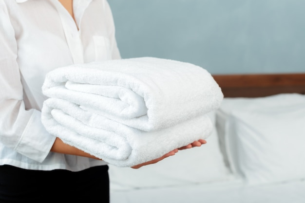Domestica con asciugamani puliti freschi durante le pulizie in una stanza d'albergo Foto Premium