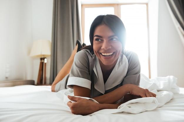 Domestica sorridente dell'hotel che si trova su un letto Foto Gratuite