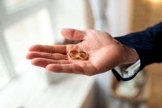 Donazione dell'anello nuziale. lo sposo tiene gli anelli Foto Premium