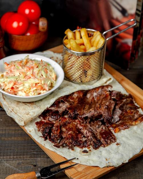 Doner di carne con patatine fritte su tavola di legno Foto Gratuite