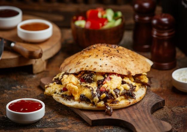 Doner kebab di manzo nel pane pita con formaggio fuso su tavola di legno Foto Gratuite