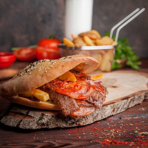 Doner vista laterale con pomodoro e patate fritte e pane in pentole a bordo Foto Gratuite
