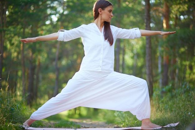 Donna a piedi nudi che si estende in natura Foto Gratuite