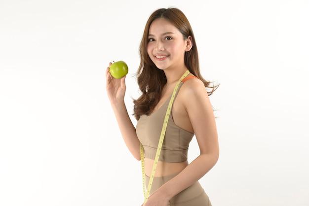 Donna abbastanza asiatica con la mela e nastro adesivo di misura su bianco Foto Premium