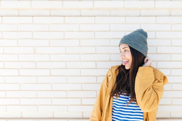 Donna abbastanza felice che attacca la sua lingua fuori davanti al muro di mattoni Foto Gratuite