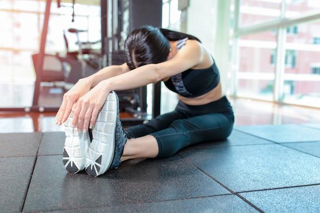 Donna adatta che allunga la sua gamba per riscaldarsi in palestra Foto Premium