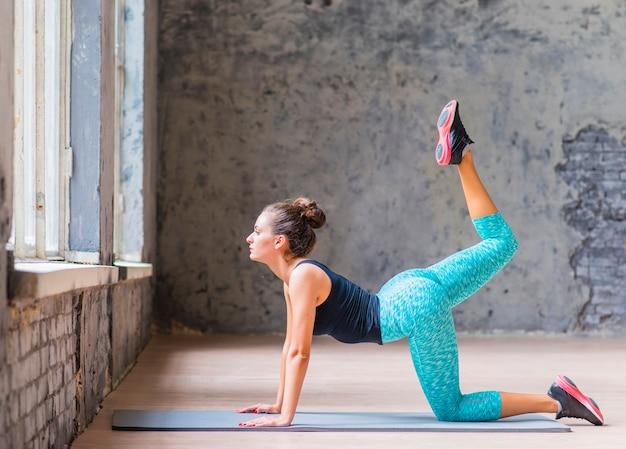 Donna adatta che fa esercizio sulla stuoia di yoga Foto Gratuite