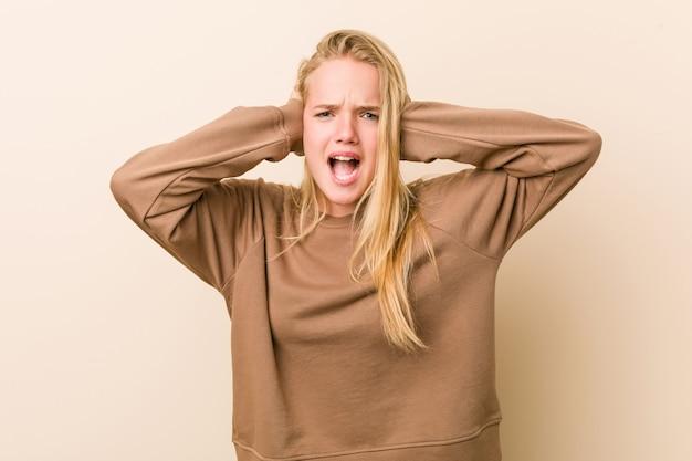 Donna adolescente carina e naturale che copre le orecchie con le mani cercando di non sentire un suono troppo forte. Foto Premium