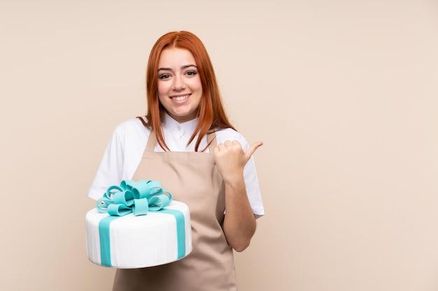 Donna adolescente rossa con una grande torta che punta verso il lato per presentare un prodotto Foto Premium
