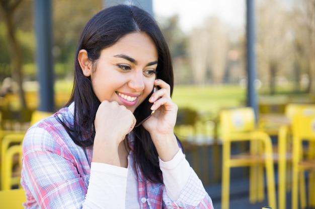 Donna adorabile sorridente che parla sul telefono cellulare in caffè della via Foto Gratuite