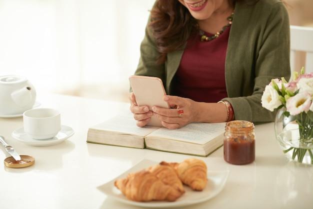 Donna adulta che chiacchiera con qualcuno che utilizza l'app messenger sul suo smartphone Foto Gratuite