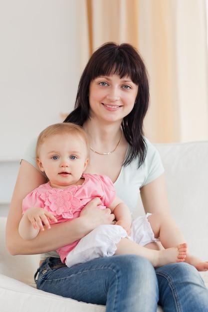 Donna affascinante che tiene il suo bambino in braccio mentre era seduto su un divano - Musica divano era ...